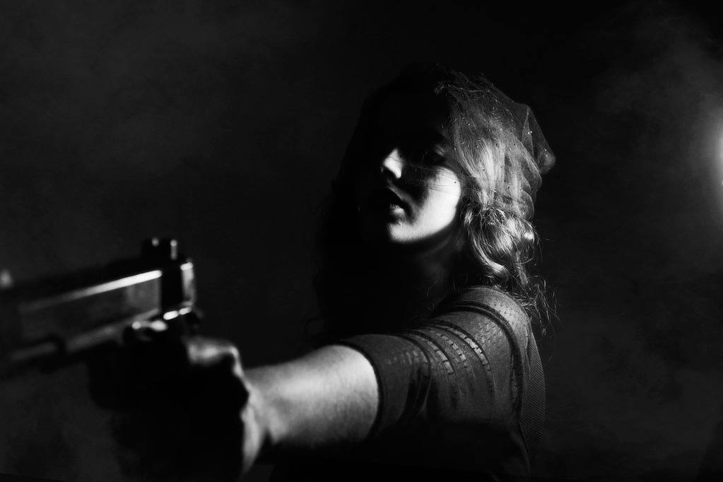 a woman pointing the gun to her target