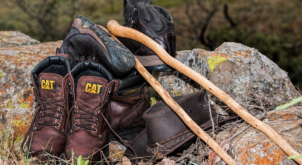 a set of hunting gear like boots, hat and sticks