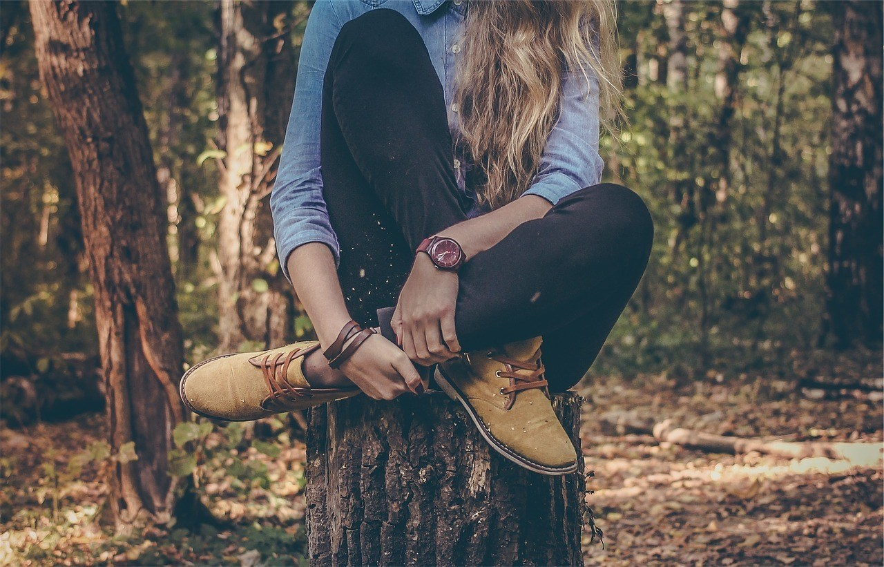 a woman wearing comfortable hunting shirts and pants and is sitting on top of a tree stump