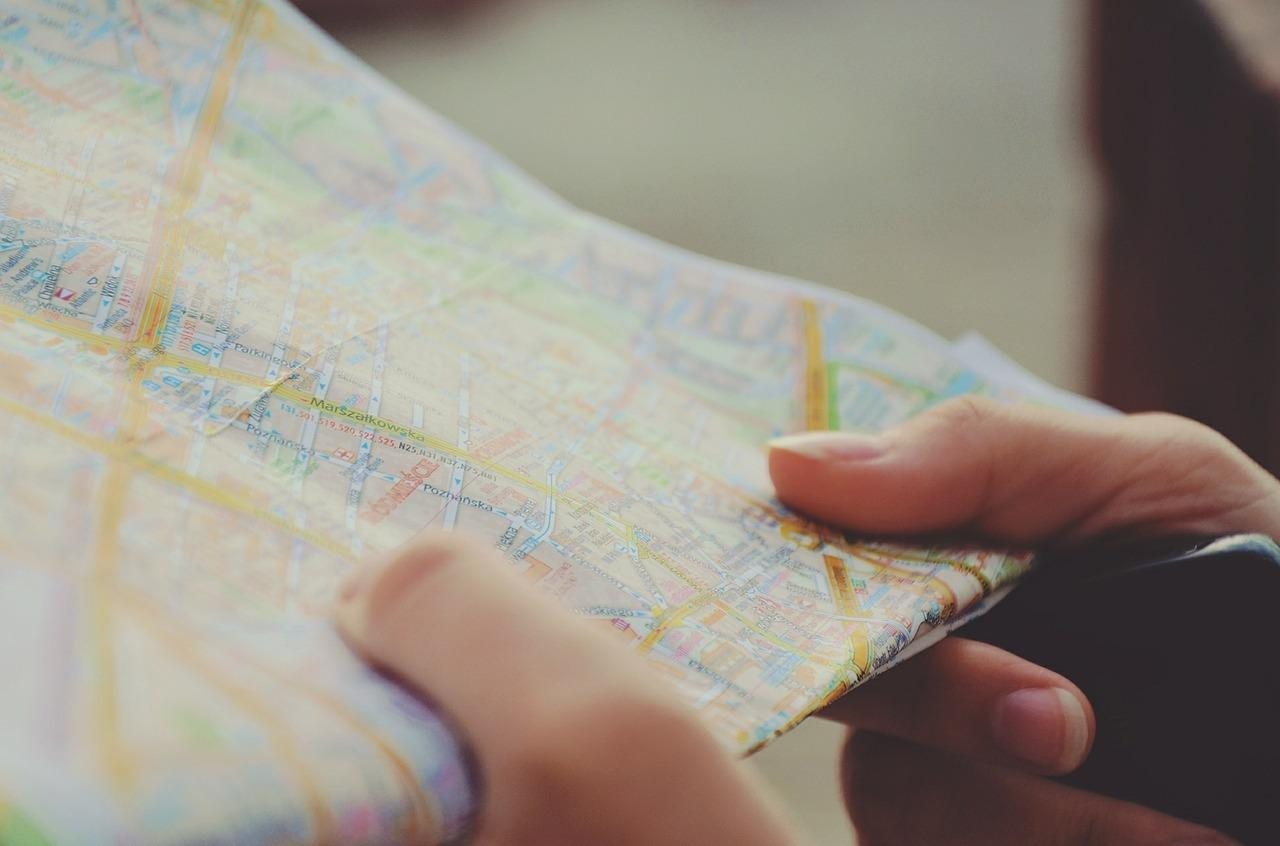 close-up photo of hands holding a road map