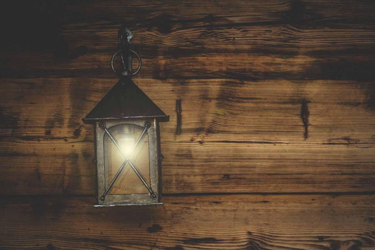a lit lantern hanging on the wooden wall