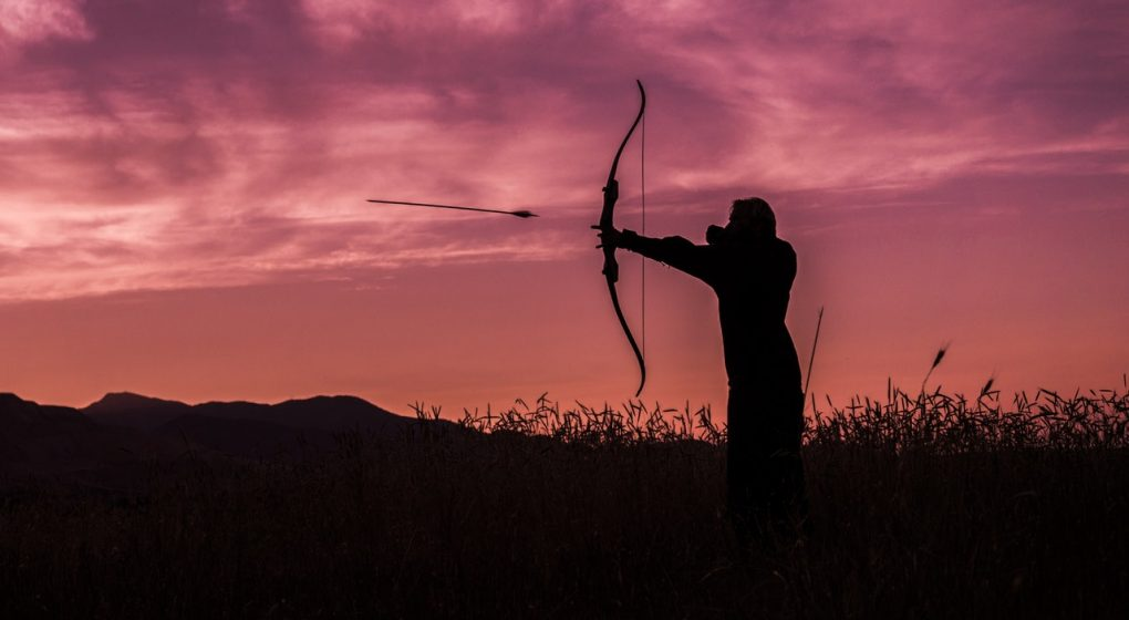 a Silhouette of a hunter shooting his bow and arrow