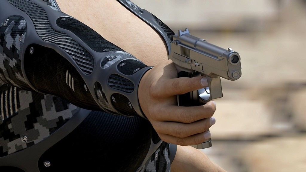 a woman using one hand to aim the handgun to her target