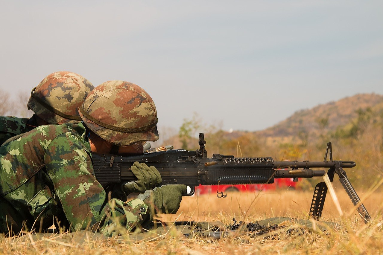 a soldier lying on the ground and aiming to shoot his firearm with a bipod