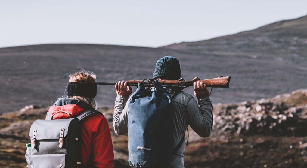 a hunter carrying the hunting rifle on his shoulders while carrying a backpack and walking with another hiker