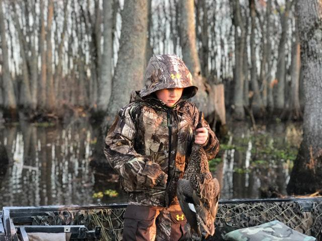 a little child holding a duck and wearing camouflage jacket, one of the gift ideas for daughters who like hunting
