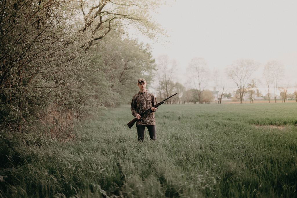 a young man wearing a cup and long sleeves while holding a hunting rifle in the middle of a field