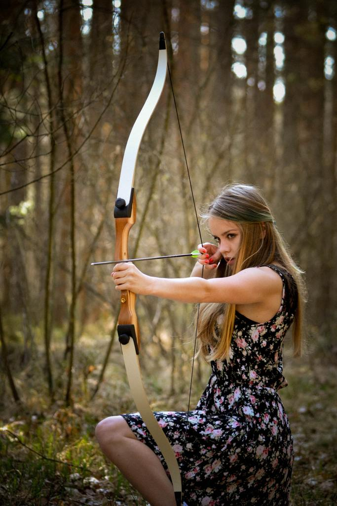 Beautiful girl is holding a bow and arrow
