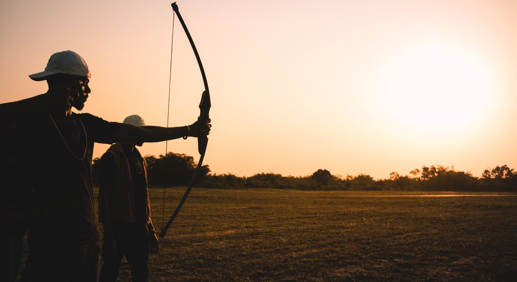A person is holding a bow and arrow and ready to hit the target and beside him is a man standing